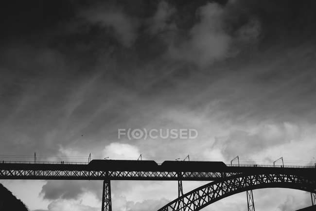 Low angle view of railway bridge over city river — Stock Photo