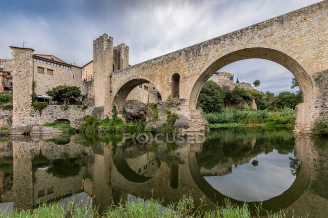 View of the medieval bridge over reflecting river surface — Stock Photo