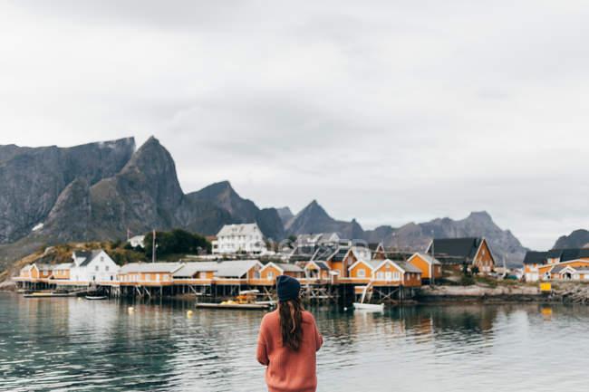 Rückansicht des Frau ländliche Gebäuden am gegenüberliegenden Ufer des Sees zu bewundern — Stockfoto