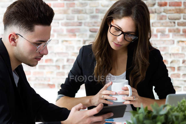 Portrait of businessman showing smartphone screen to colleague during coffee break . — Stock Photo