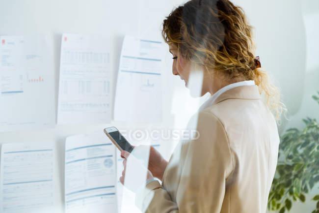 Vista lateral da mulher de negócios digitando no smartphone no escritório — Fotografia de Stock