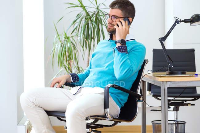 Портрет молодой бизнесмен, сидя в кресле и говорить на смартфон в современном офисе. — стоковое фото