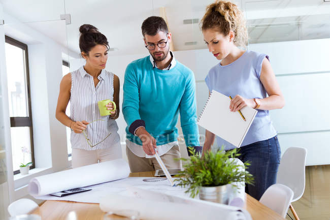 Portrait of group of business people discussing project documentation in modern office. — Stock Photo