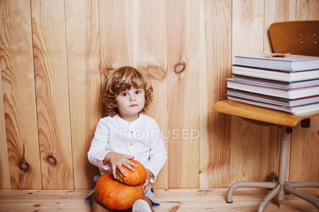 Little kid sitting on floor with pumpkinsand looking at camera — Stock Photo