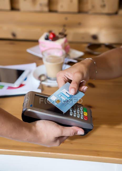 Mains de récolte payer avec carte de crédit au café — Photo de stock