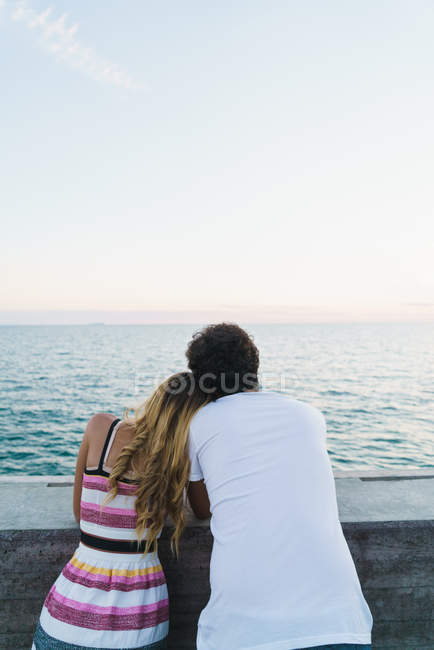 Rear view of couple leaning on parapet and admiring seascape — Stock Photo