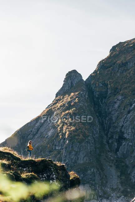 Vista in lontananza della donna che propone alla scogliera in montagne — Foto stock
