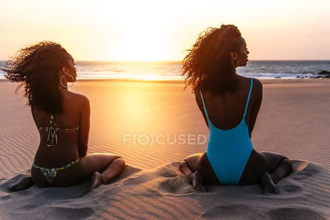 Vista posteriore della donna che si siede sulla spiaggia tropicale nel tramonto — Foto stock