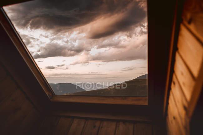 Paisaje nuboso dramático sobre el paisaje de montaña visto a través de la ventana - foto de stock