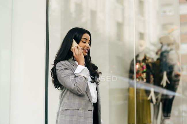 Боковой вид o предприниматель разговаривает по телефону возле витрины — стоковое фото