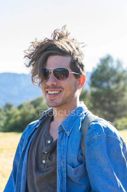 Portrait of laughing man in casual clothing and sunglasses at field — Stock Photo