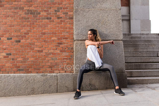 Sportive woman leaning  on wal with and warming up shoulder at street — Stock Photo