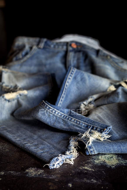 Close up of teared blue jeans pants on dark table. — Stock Photo