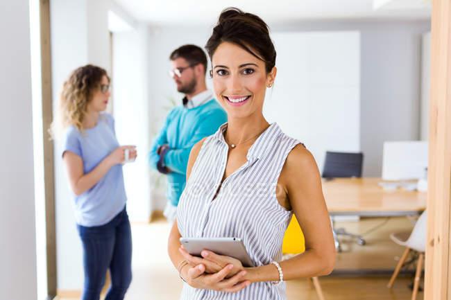 Портрет улыбающейся деловой женщины, смотрящей в камеру в современном офисе . — стоковое фото
