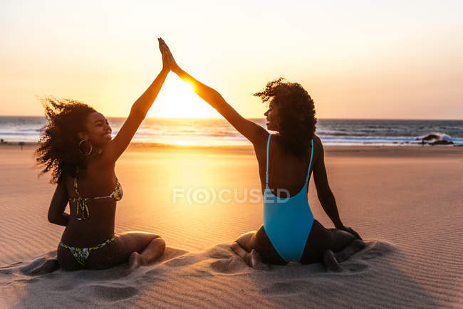 Rear view of women sitting on tropical beach and giving high five over sunset sky on background — Stock Photo