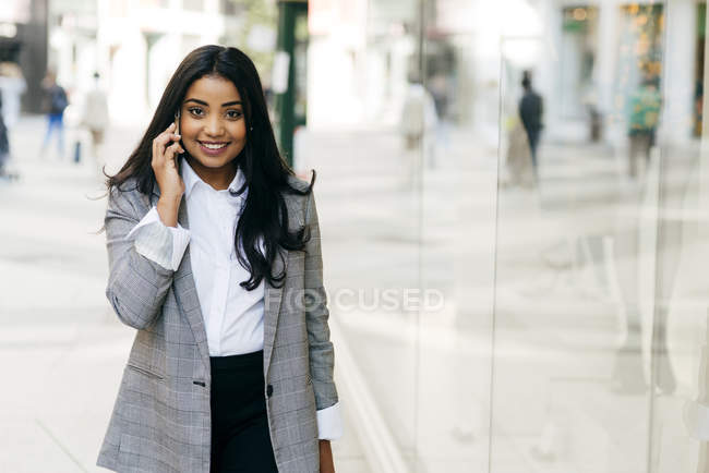 Smiling businesswoman talking phone and looking at camera — Stock Photo