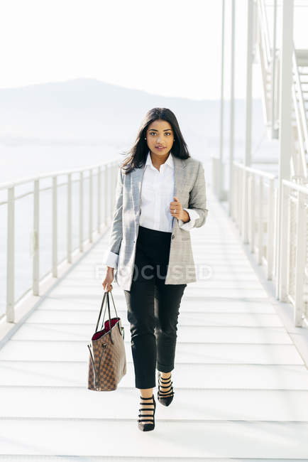 Front view of elegant woman in jacket carrying handbag and looking at camera on balcony passage — Stock Photo