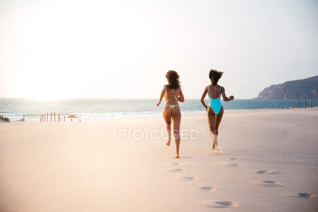 Vista posteriore di due donne che corrono sulla spiaggia al tramonto — Foto stock
