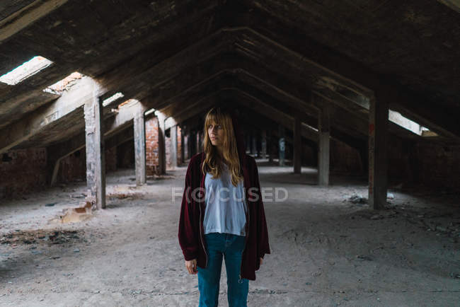 Brunette woman in red hoodie jacket posing in derelict loft — Stock Photo