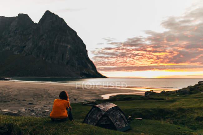 Vue arrière de la femme assise sur une colline près de la tente et regardant l'aube seascpe — Photo de stock