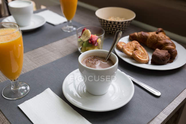Cup of coffee with different pastry on cafe table — Stock Photo