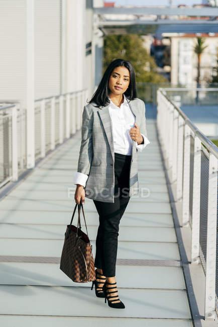 Elegant businesswoman in jacket posing on balcony passage — Stock Photo