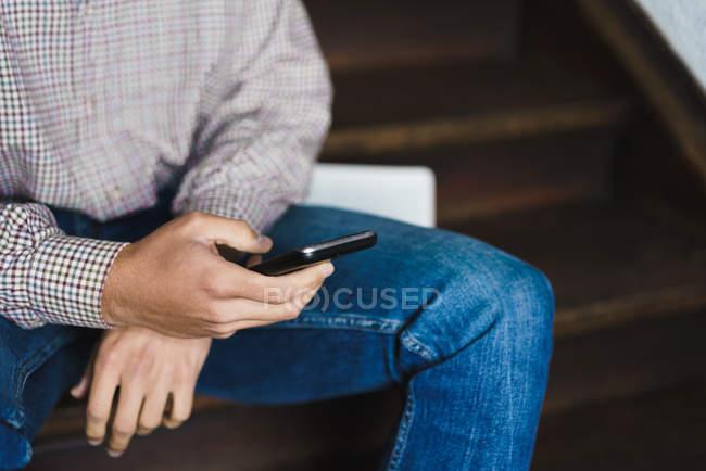 Crop uomo seduto sulle scale e la navigazione smartphone — Foto stock
