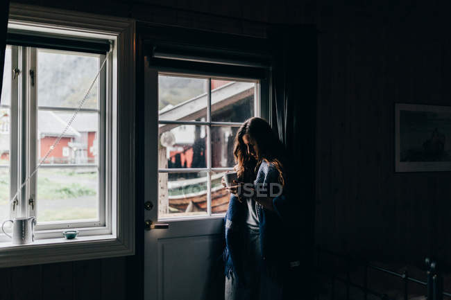 Side view of woman standing near window in dark room and looking down in mug — Stock Photo