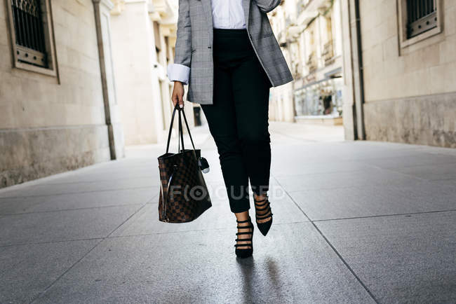 Low section of female with handbag walking at street — Stock Photo