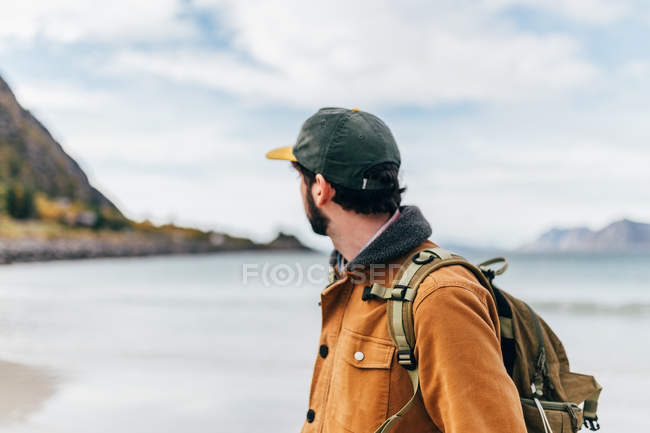 Side view of tourist man posing at lake in mountains and looking away — Stock Photo