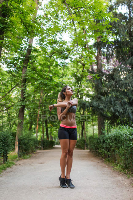 Athletic girl warming up shoulders before workout in summer park — Stock Photo