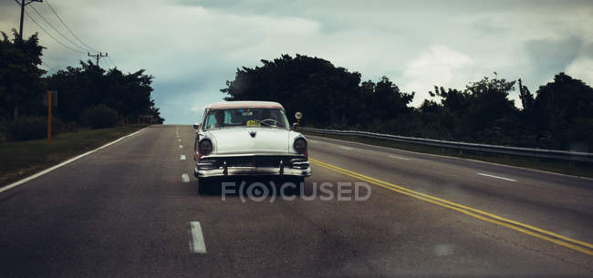 CUBA - AUGUST 27, 2016: View of white retro car driving on empty highway. — Stock Photo
