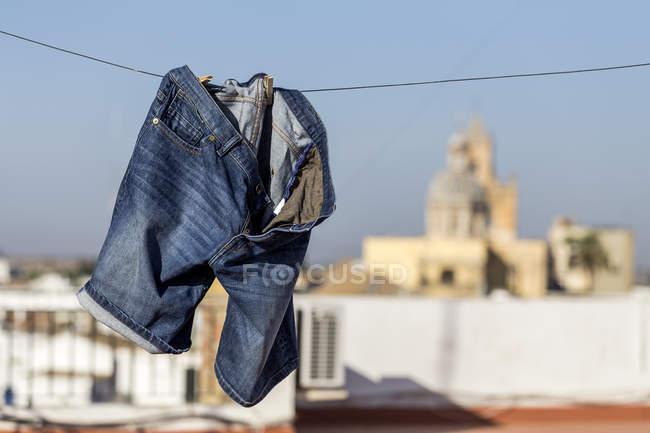 Calça jeans azul curta pendurado no varal sobre paisagem urbana turva — Fotografia de Stock