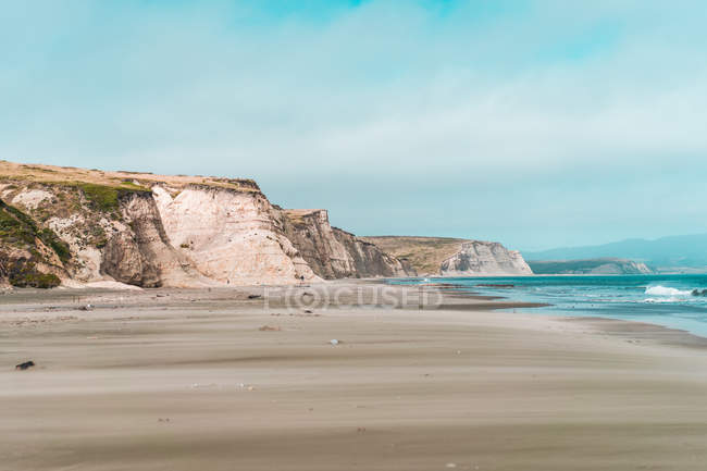 Scenic view of empty sandy beach and coastal cliffs — Stock Photo