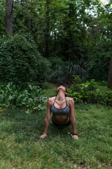 Vue de face de la femme en forme effectuant yoga asana dans le parc — Photo de stock