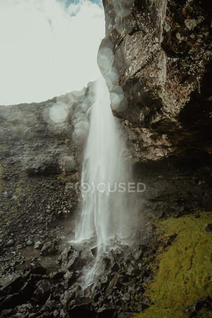 Захватывающий вид на водопад поток падает со скалы — стоковое фото