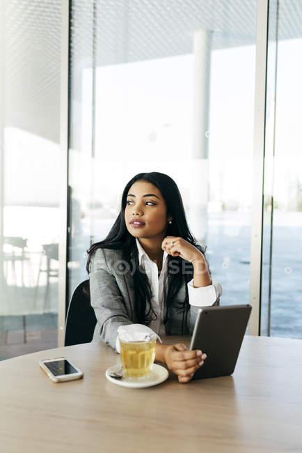 Портрет деловой женщины, сидящей за столиком кафе с планшетом — стоковое фото