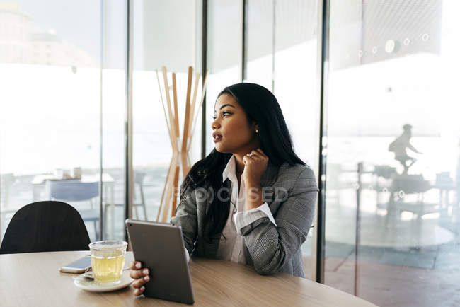 Elegant businesswoman  with tablet sitting at table and looking away — Stock Photo