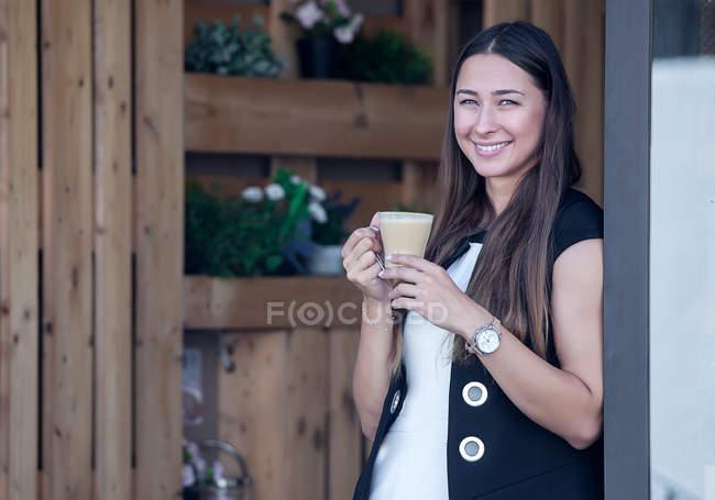 Усміхається жінка позує в пекарні з кави — стокове фото