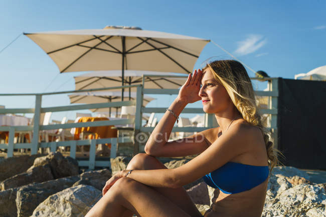 Side view of blonde girl in bikini sitting on tropical resort beach and looking away. — Stock Photo