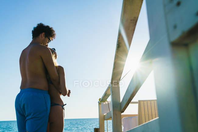 Vue arrière d'embrasser un couple amoureux admirant le paysage marin sur la plage — Photo de stock