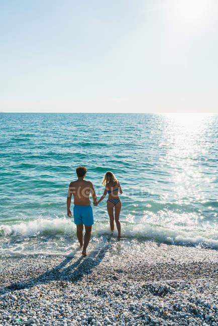 Vue arrière du couple en cours d'exécution dans les vagues de surf — Photo de stock