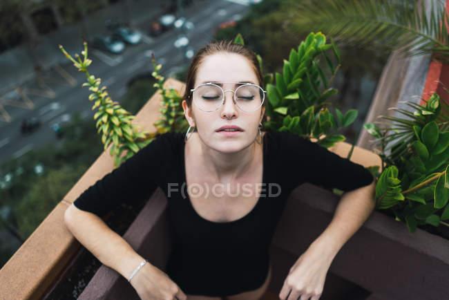 Vista basso angolo di ragazza in occhiali in posa sul balcone con gli occhi chiusi — Foto stock