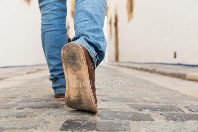 Männliche Beine treten auf gepflasterten Stadtweg — Stockfoto
