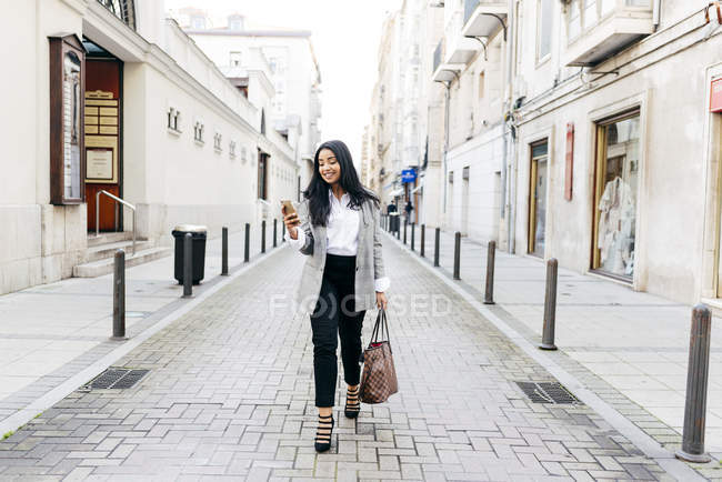 Smiling businesswoman walking with phone in hand on street — Stock Photo
