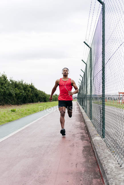 Front view of man wearing headphones running on track along fence — Stock Photo