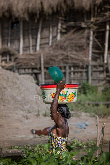 BENIN, AFRICA - AUGUST 31, 2017: Side view of woman with bowl on head — Stock Photo