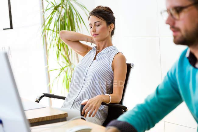 Портрет уставшей деловой женщины, сидящей в кресле с закрытыми глазами и трогательной шеей . — стоковое фото