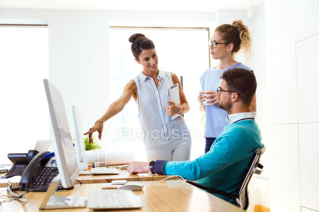 Portrait of businesswoman pointing at monitor to colleagues in modern office. — Stock Photo