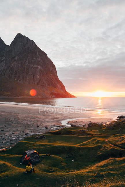 Rückansicht der Frau sitzen auf Hügel nicht weit von Zelt und genießen atemberaubende Aussicht auf den Sonnenuntergang an der Bucht. — Stockfoto